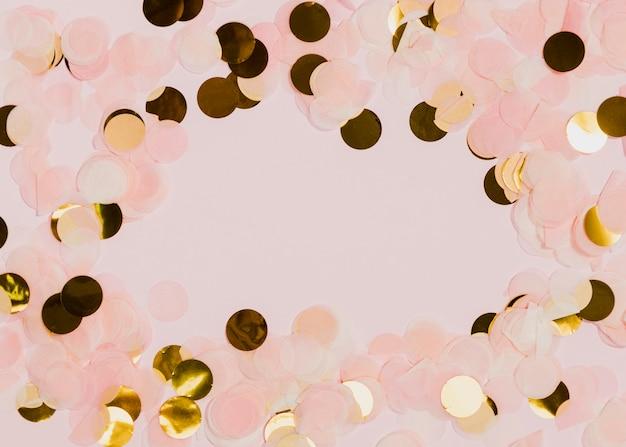 Konfettis an den neuen jahren party mit rosafarbenem hintergrund
