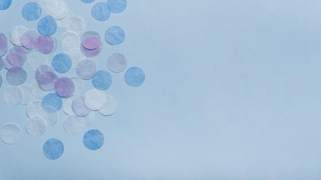 Konfettis auf einem blauen hintergrund mit kopienraum