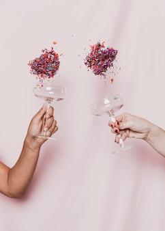 Konfettis, die aus gläsern heraus an der party der neuen jahre fliegen