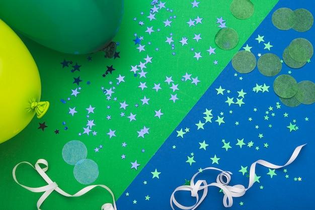 Konfettisterne und -ballone auf buntem hintergrund