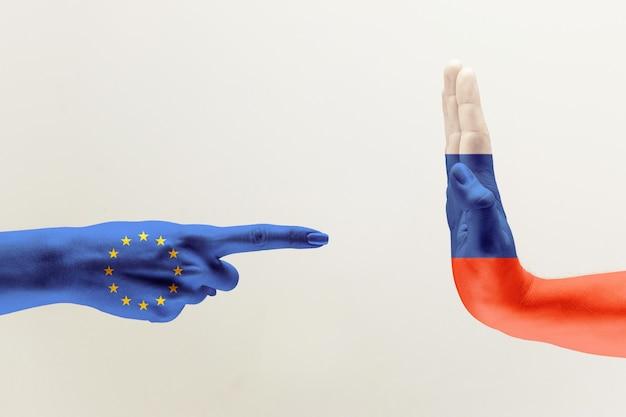 Konfrontation, uneinigkeit der länder. weibliche und männliche hände, die in flaggen der europäischen einheit und russlands lokalisiert auf grauem hintergrund gefärbt sind. konzept politischer, wirtschaftlicher oder sozialer aggressionen.