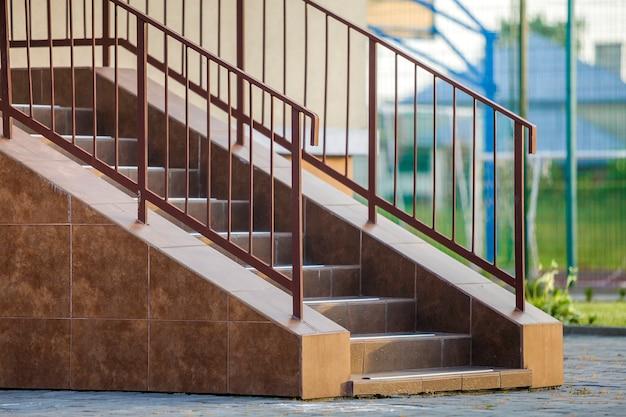 Konkrete treppe draußen bedeckt mit keramikfliesen mit metallgeländern.