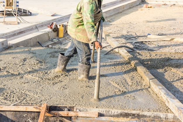 Konkretes gießen während der kommerziellen betonierfußböden von gebäuden in der baustelle.