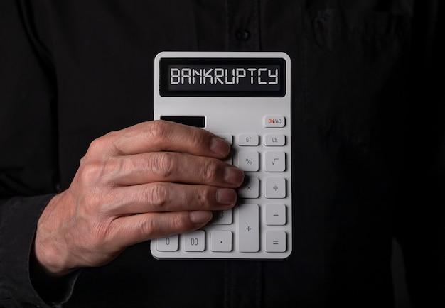 Konkurswort auf taschenrechner in der hand über schwarzem hintergrund