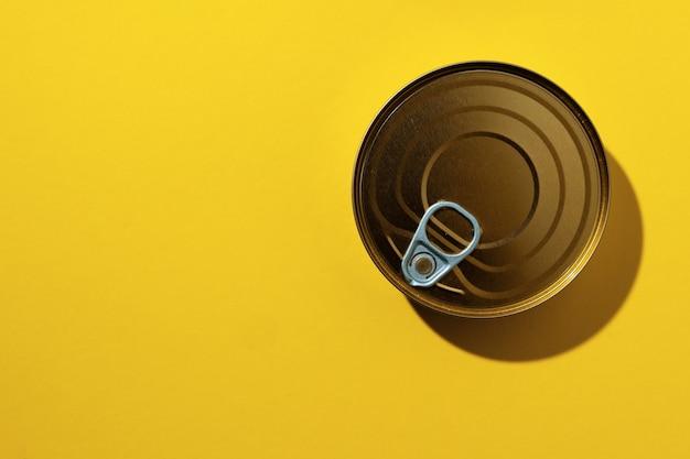Konservendose auf gelber studiofläche