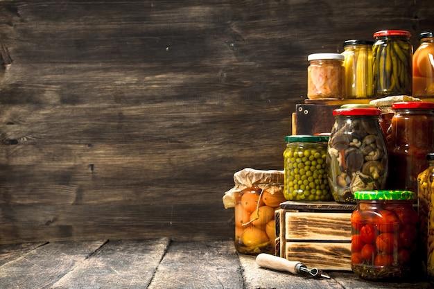 Konserviert pilze und gemüse in einer box. auf einem holztisch.