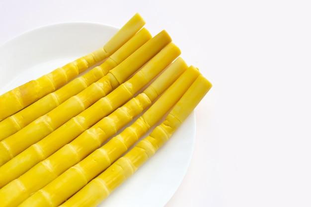 Konservierte bambussprossen in weißer platte auf weißem hintergrund.
