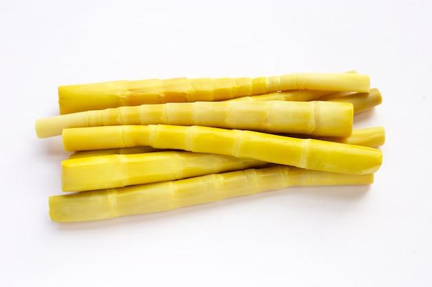 Konservierte bambussprossen in weißer schüssel auf gelbem hintergrund.