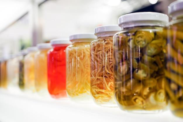 Konservierte, eingelegte gurken und lebensmittelzutaten befinden sich in den regalen. schön arrangiert.