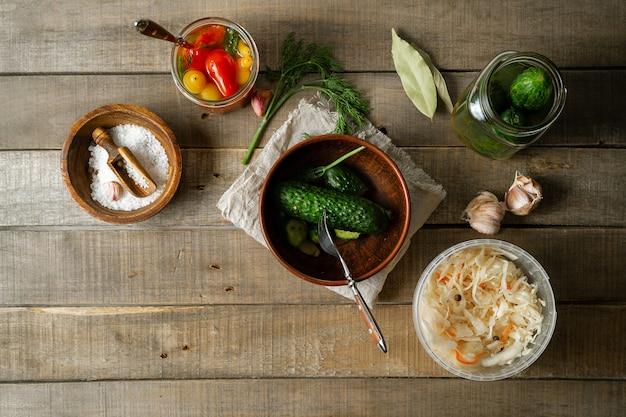 Konservierte gurken, kohl, tomaten auf rustikalem hölzernem hintergrund. draufsicht, horizontales bild