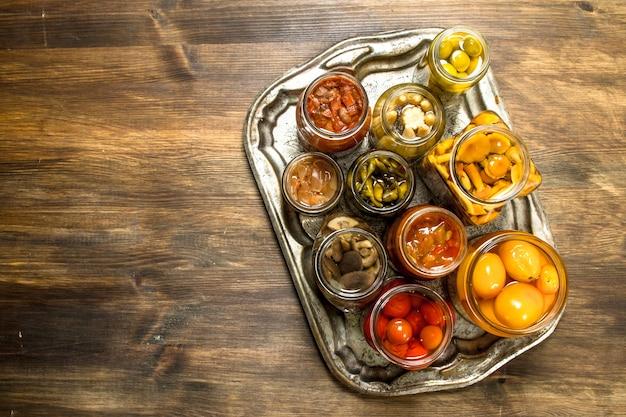 Konservierte pilze und gemüse auf stahltablett auf holztisch.