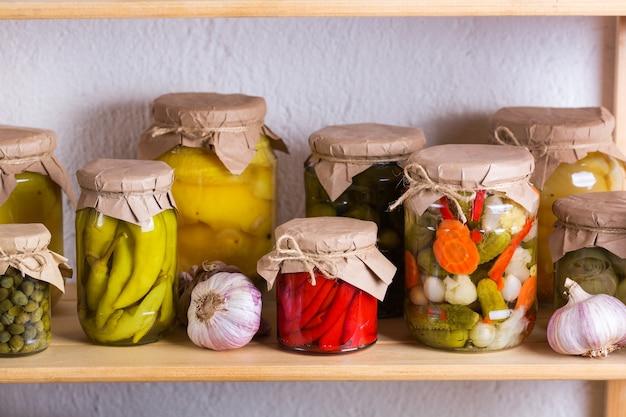 Konservierte und fermentierte lebensmittel. auswahl an hausgemachten gläsern mit verschiedenen eingelegten und marinierten gemüsen auf einem regal im lagerraum. hauswirtschaft, hauswirtschaft, ernteerhaltung