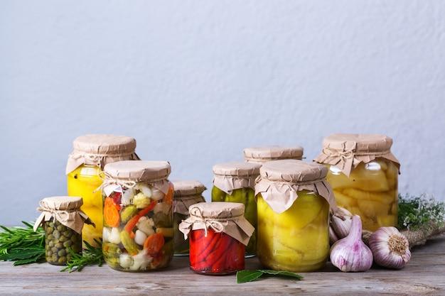 Konservierte und fermentierte lebensmittel. auswahl an hausgemachten gläsern mit verschiedenen eingelegten und marinierten gemüsesorten auf einem holztisch. hauswirtschaft, hauswirtschaft, ernteerhaltung