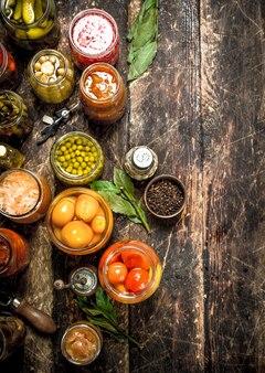 Konserviertes gemüse in gläsern mit seemann auf holztisch.