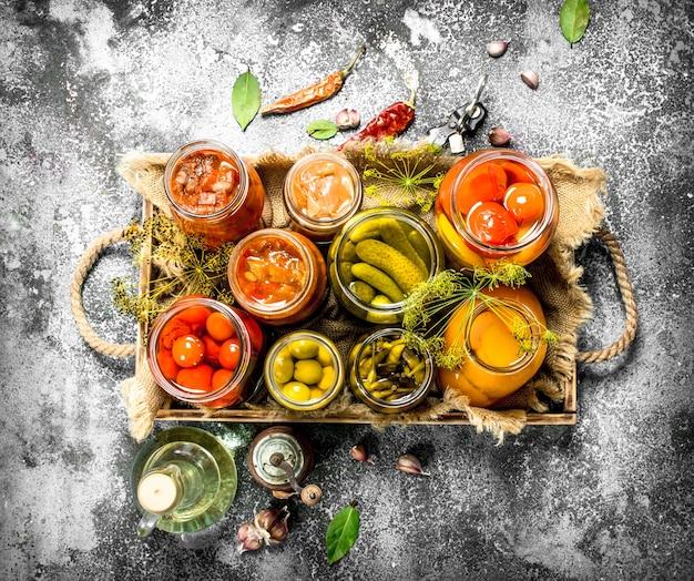 Konserviertes gemüse mit pilzen auf einem alten tablett. auf einem rustikalen tisch.