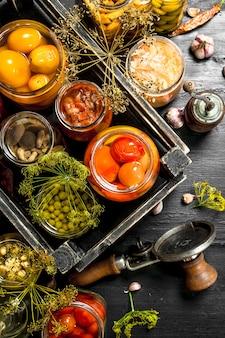 Konserviertes gemüse und pilze in einer schachtel mit seemann auf schwarzer tafel.