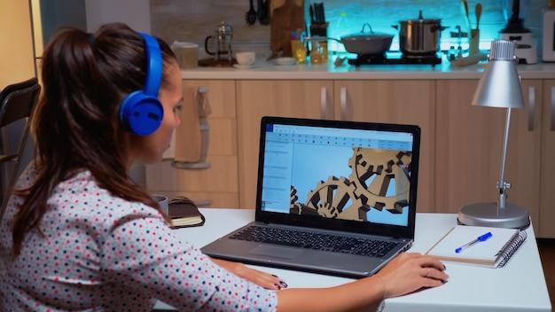 Konstruktionsingenieur, der von zu hause aus an einer 3d-komponente im cad-programm auf einem laptop arbeitet. industrielle weibliche angestellte, die prototypidee auf pc studiert und cad-software auf dem gerätedisplay zeigt software