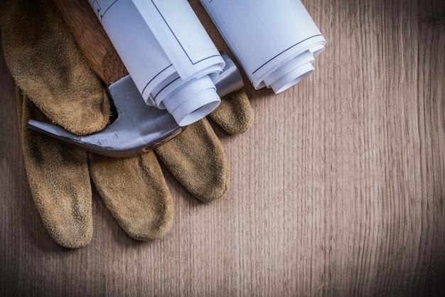 Konstruktionszeichnungen schutzhandschuhe und klauenhammer auf holzbrett.