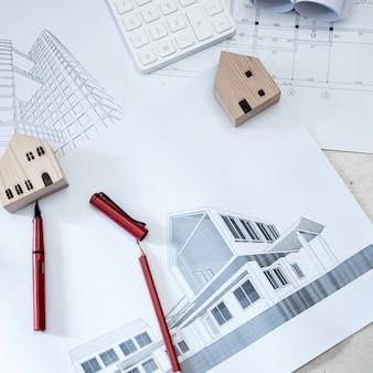 Konstruktionszeichnungen, taschenrechner und holzhausmodelle auf betonboden