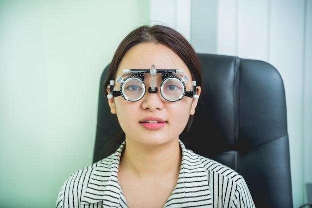 Konsultation mit einem augenarzt. junge asiatische frau im klinikbüro.