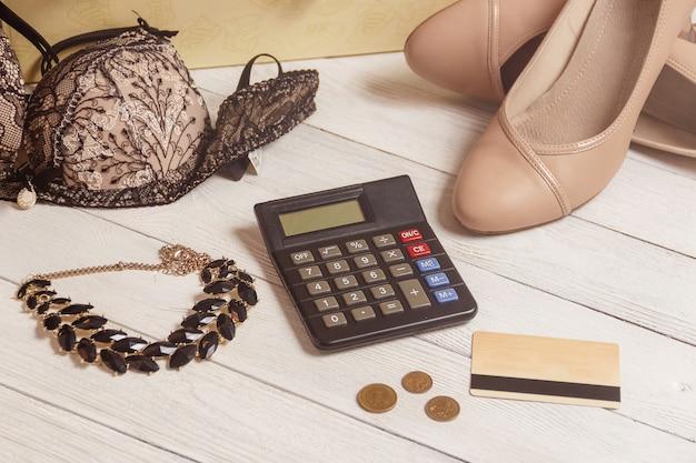 Konsum- und verkaufskonzept - taschenrechner, frauenkleidung, zubehör.