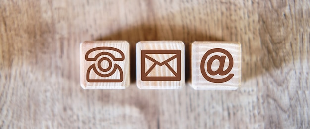 Kontakt icons brief e-mail-nachricht telefon-konzept auf einem hölzernen hintergrund