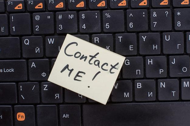 Kontaktieren sie mich wörter auf briefpapier geschrieben. hinweis zur schwarzen tastatur.