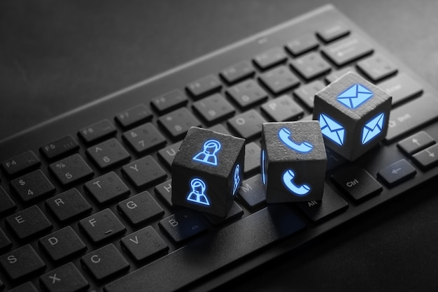 Kontaktieren sie uns geschäftssymbol auf schwarzer computertastatur mit leuchten im dunkeln