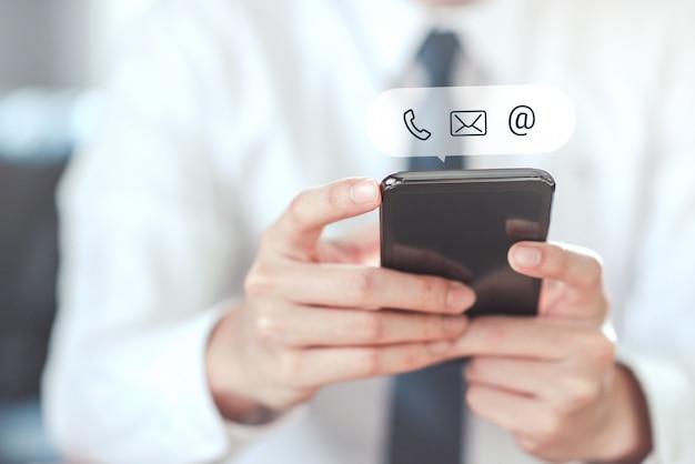 Kontaktieren sie uns, hand des geschäftsmannes, der mobiles smartphone mit symbol hält. cutomer-unterstützung.