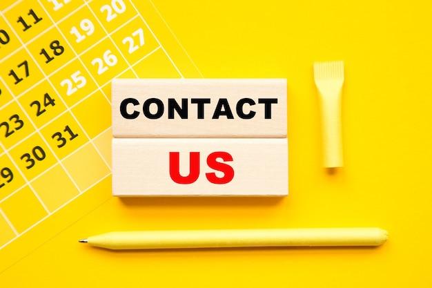 Kontaktieren sie uns-inschrift auf würfeln, abstrakter kalender, gelber stift auf gelbem hintergrund