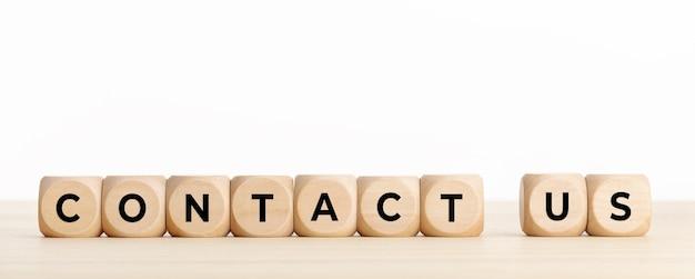 Kontaktieren sie uns konzeptbanner. holzklötze mit text auf dem schreibtisch. speicherplatz kopieren