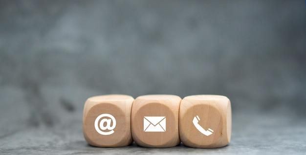 Kontaktieren sie uns symbol telefon e-mail auf holzwürfel kundenservice und support