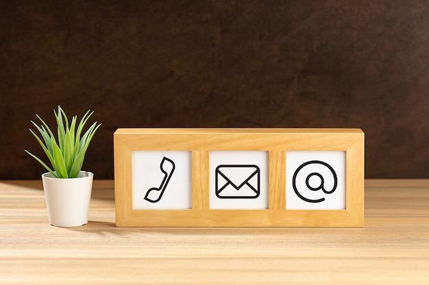 Kontaktieren sie uns symbole im modernen holzrahmen auf dem schreibtisch. braune strukturierte wand. platz kopieren