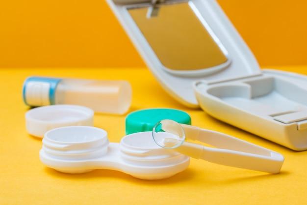 Kontaktlinsen auf einer pinzette über einem offenen behälter zum aufbewahren und reinigen von linsen, etui und flasche