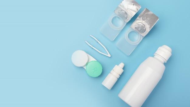 Kontaktlinsen mit kochsalzlösung in der flasche, pinzette, augentropfen, plastikhülle mit lösung