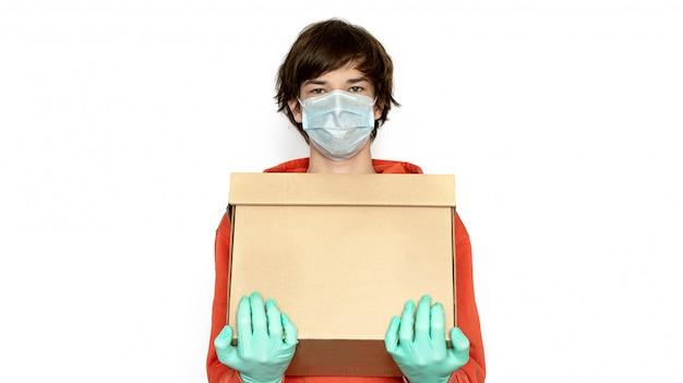 Kontaktlose lieferung. ein mann in einer medizinischen maske und handschuhen hält eine schachtel. isolieren, speicherplatz kopieren. coronavirus isolation online-lieferung von produkten und waren, einkaufen