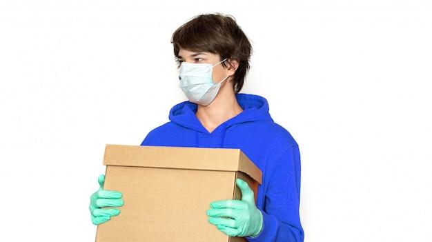 Kontaktlose lieferung. ein mann in einer medizinischen maske und handschuhen hält eine schachtel. kopierraum isolieren.