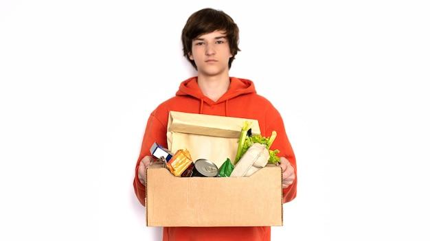 Kontaktlose lieferung. mann in einer medizinischen maske und handschuhen hält eine box.