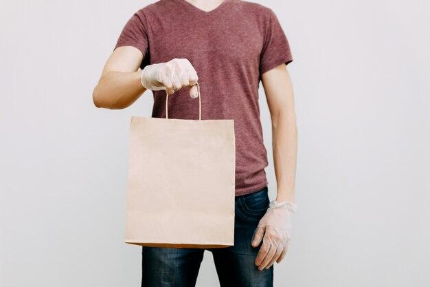 Kontaktlose lieferung von lebensmitteln durch einen maskierten und behandschuhten kurier aus einem geschäft oder restaurant.