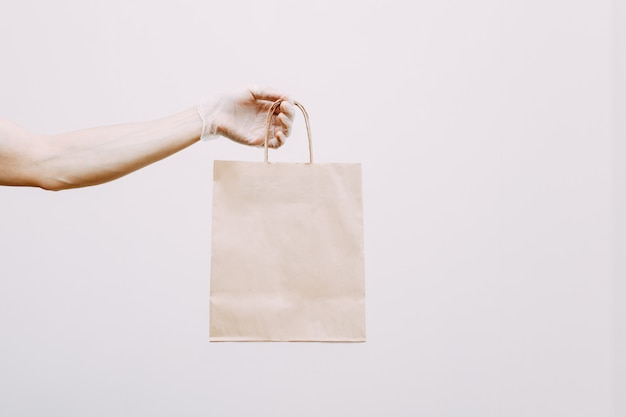Kontaktlose lieferung von lebensmitteln in öko-verpackung durch einen behandschuhten kurier aus einem geschäft oder restaurant. die hand eines mannes mit einem paket auf einem weißen hintergrund.