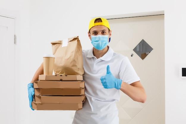 Kontaktlose pizzalieferung. pizzakarton. lieferbote, der kartons in medizinischen gummihandschuhen und maske hält. schneller und kostenloser liefertransport. online-shopping und express-lieferung. quarantäne