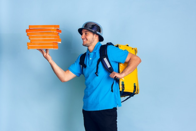 Kontaktloser lieferservice während der quarantäne. der mensch liefert während der isolierung lebensmittel und einkaufstaschen. emotionen des lieferers isoliert auf blau