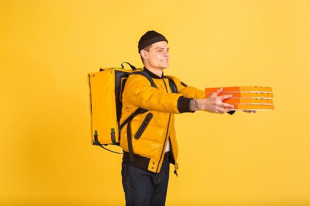 Kontaktloser lieferservice während der quarantäne. der mensch liefert während der isolierung lebensmittel und einkaufstaschen. emotionen des lieferers isoliert auf gelb