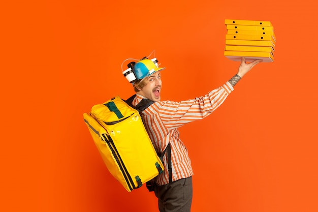 Kontaktloser lieferservice während der quarantäne. der mensch liefert während der isolierung lebensmittel und einkaufstaschen. emotionen des lieferers isoliert auf orange