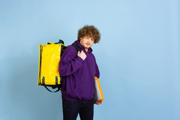 Kontaktloser lieferservice während der quarantäne mann liefert lebensmittel und einkaufstüten während der isolierung emotionen des lieferers isoliert auf blauer wand