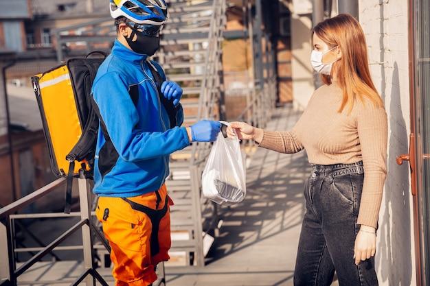 Kontaktloser lieferservice während der quarantäne. mann liefert während der isolation lebensmittel und einkaufstüten. klopfen an der tür und lässt die ware, bis der kunde sie abholt. sicherheit, empfangen, abstand halten.