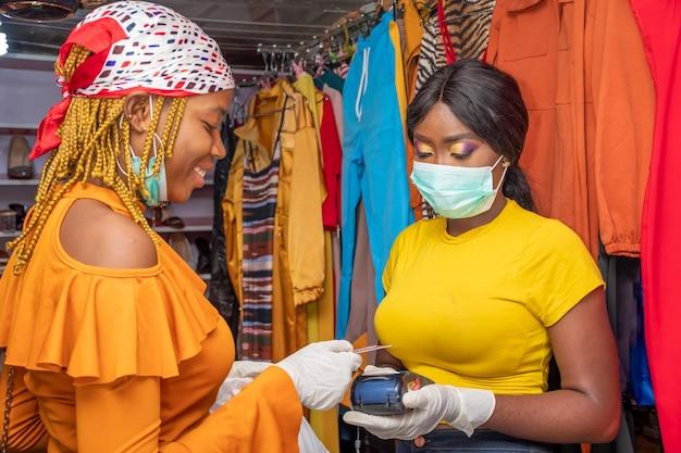 Kontaktloses bezahlen, tragen von gesichtsmasken und handschuhen, begrenzung der ausbreitung des coronavirus