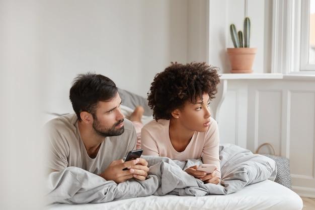 Kontemplative familienpaare benutzen handys, konzentrieren sich beiseite und liegen morgens im bett