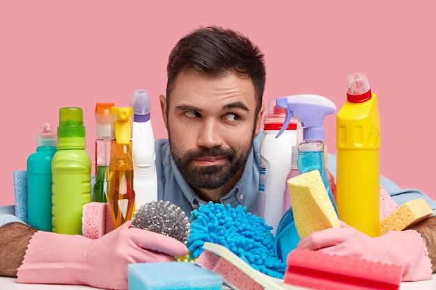 Kontemplativer mann mit dunklen stoppeln, trägt gummihandschuhe, posiert in der nähe vieler reinigungsmittel, hält schwamm, geht geschirr spülen, schrubbt badewanne