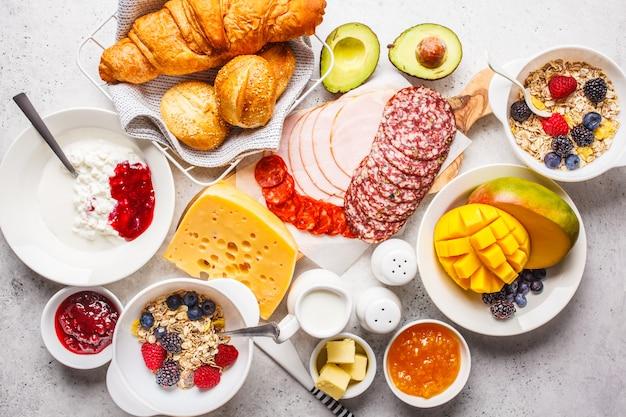 Kontinentaler frühstückstisch mit croissants, marmelade, schinken, käse, butter, müsli und obst.